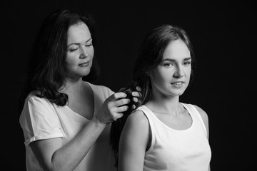Black and white portrait of woman doing hair of her daughter on dark background