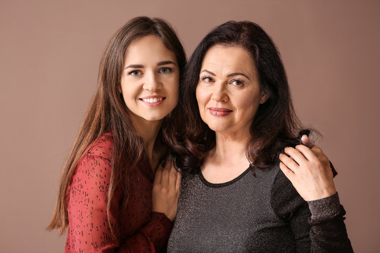 Portrait of young woman with her mother on color background