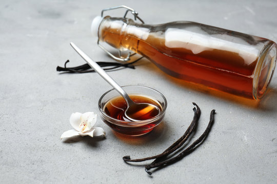 Glass bowl and bottle with vanilla extract on table