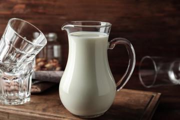 Jug of fresh milk on table