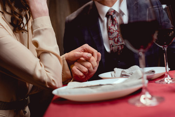 partial view of couple holding hands while having romantic date in restaurant