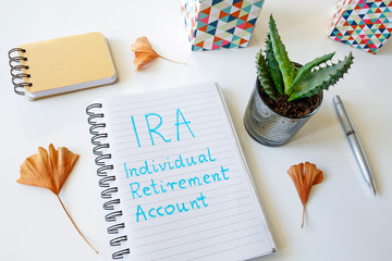 IRA Individual Retirement Account written in a notebook on white table