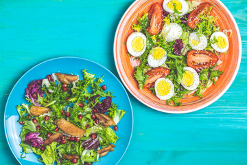 Two healthy delicious salads on turquoise table surface.