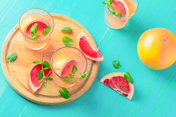 Pink alcoholic cocktail with grapefruit, ice and mint