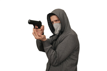 The man in a sports gray jacket and in a mask on a face shoots with the gun. White background