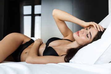 Beautiful young woman wearing black lingerie laying