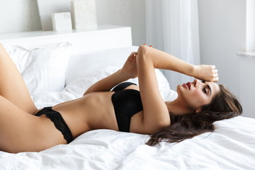 Brunette woman wearing lingerie lies in bed indoors in bedroom.
