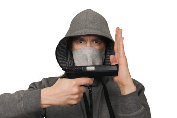 The man in a mask with a gun shows hands signs. White background