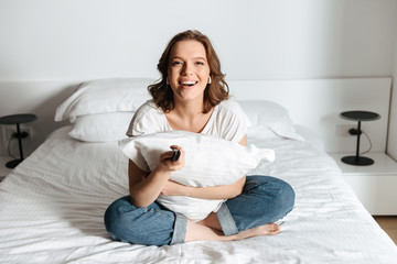 Attractive young woman sitting on bed at home