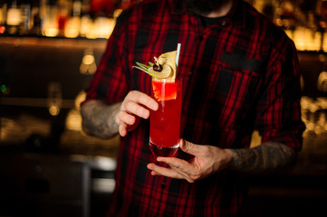 Bartender serving a glass of a Hurricane Punch cocktail on the bar counter
