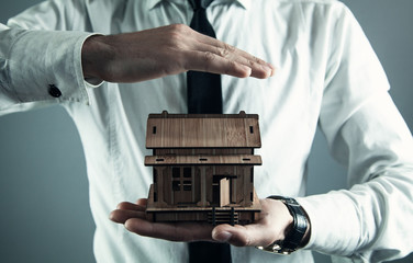 Real estate agent protect wooden house. Real estate concept