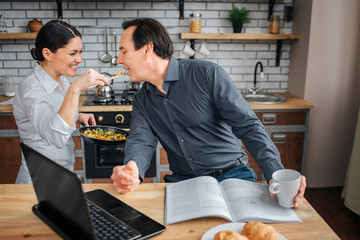 Cheerful adult woman give man to taste food. They stand in kitchen. Woman smile. She hold frying pan with food on it. Man sit at table and keep mouth opened. He works there.