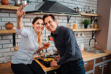 Cheerful couple stand together in kitchen. She sit at stove and take selfie. Guy pose and fry food. He smile.