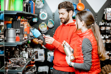 Young couple dressed in red sportswear choosing dishes for camping in the shop with travel equipment