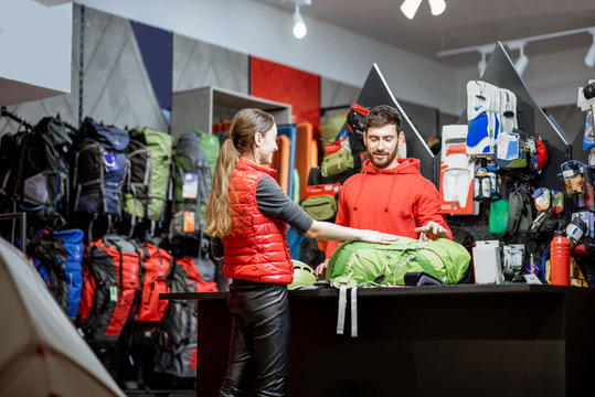 Young woman buying some sports goods standing with salesman at the counter of the shop
