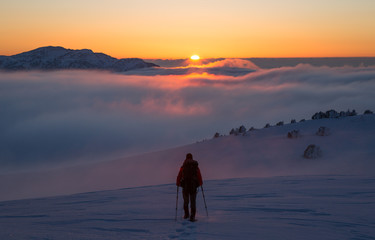 Hiker walking on snowshoes in the snow-covered mountains during a colorful, winter sunset. Vercors, France.