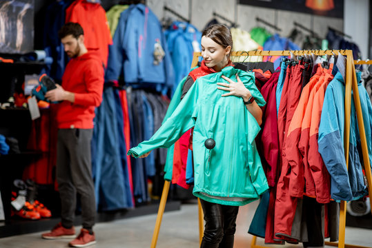 Young woman choosing winter clothes trying windbreaking jacket in the sports shop
