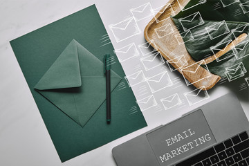 Green paper for letter template by laptop on white marble background with email marketing and icons