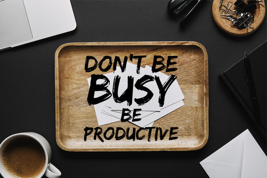 "Wooden tray with business cards and ""do not be busy, be productive"" inspiration with office supplies"