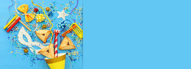 Purim celebration concept (jewish carnival holiday) over wooden blue background.