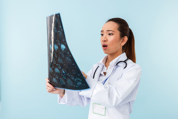 Shocked woman doctor posing isolated over blue wall background with x-ray.