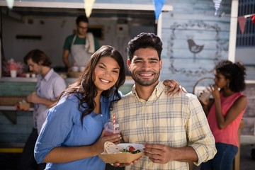Smiling couple standing with snacks and juice