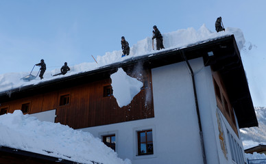 Austrian army members shovel snow on a rooftop after heavy snowfall in Werfenweng