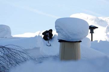 An Austrian army member shovels snow on a rooftop after heavy snowfall in Werfenweng