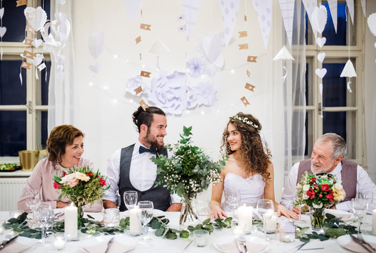 A young couple with parents sitting at a table on a wedding, looking at each other.