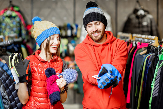 Young and happy couple trying winter clothes wearing colorful hats and gloves in the sports shop