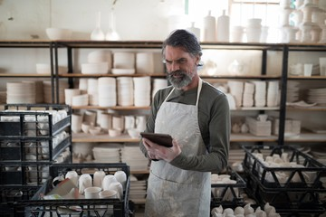 Focused potter using tablet surrounded by work