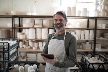 Smiling potter using tablet surrounded by work