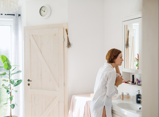 A young woman putting on a make-up in the morning in a bathroom. Fotoväggar
