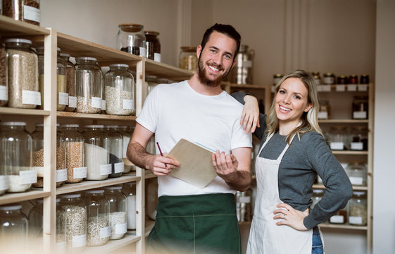 Two shop assistants standing in zero waste shop, checking stock.