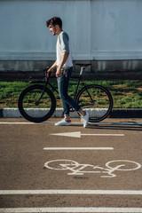 Young man pushing commuter fixie bike on bicycle lane