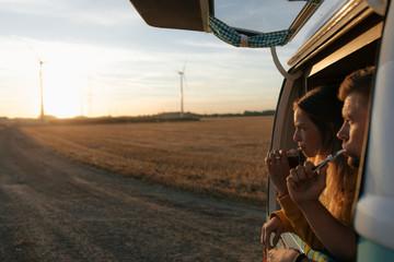 Couple brushing teeth in camper van in rural landscape at sunset