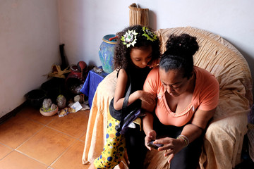 Anthonella Peralta looks at photos sent by her mother Yusmarlys Orozco on grandmother Aura's phone, in their home in the slum Cota 905 in Caracas