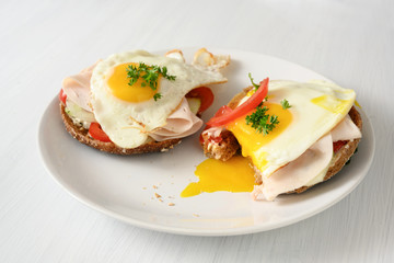 fried egg with running yolk on wholemeal bread rolls with tomato, cucumber and cooked ham, healthy hearty breakfast on a white table, copy space