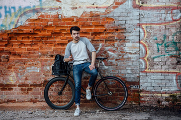 Young man with commuter fixie bike standing at brick wall with cell phone and earphones