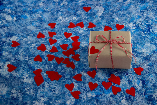 One present wrappend in craft paper tied with baker`s twine string. Gift on a blue background and a scattering of hearts.