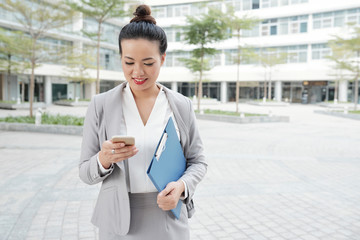 Positive pretty Asian businesswoman checking messages in her smartphone when standing outdoors