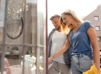 Belgium, Tongeren, happy young couple looking in shop window of an antique shop