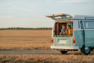 Happy young couple lying in camper van in rural landscape