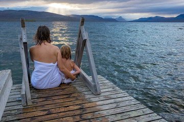 Finland, Lappland, Kilpisjaervi, mother and daughter sitting outside on boardwalk, rear view