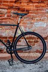 Detail of a customised commuter fixie bike at brick wall