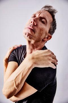 Portrait of egocentric mature man hugging himself