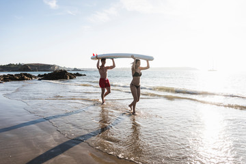 France, Brittany, young couple carrying an SUP board at the sea together