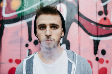 Young man standing in front of graffiti, smoking electronic cigarette