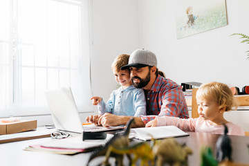 Father working at home, using laptop with his children on his lap