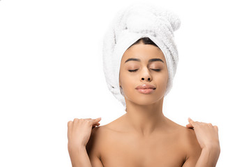 relaxed naked african american woman with closed eyes and towel on head touching shoulders isolated on white